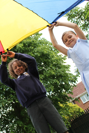 2 pupils playing with a kite