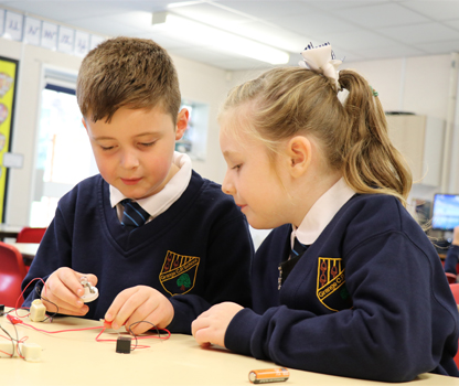A picture of 2 pupils working with maths blocks